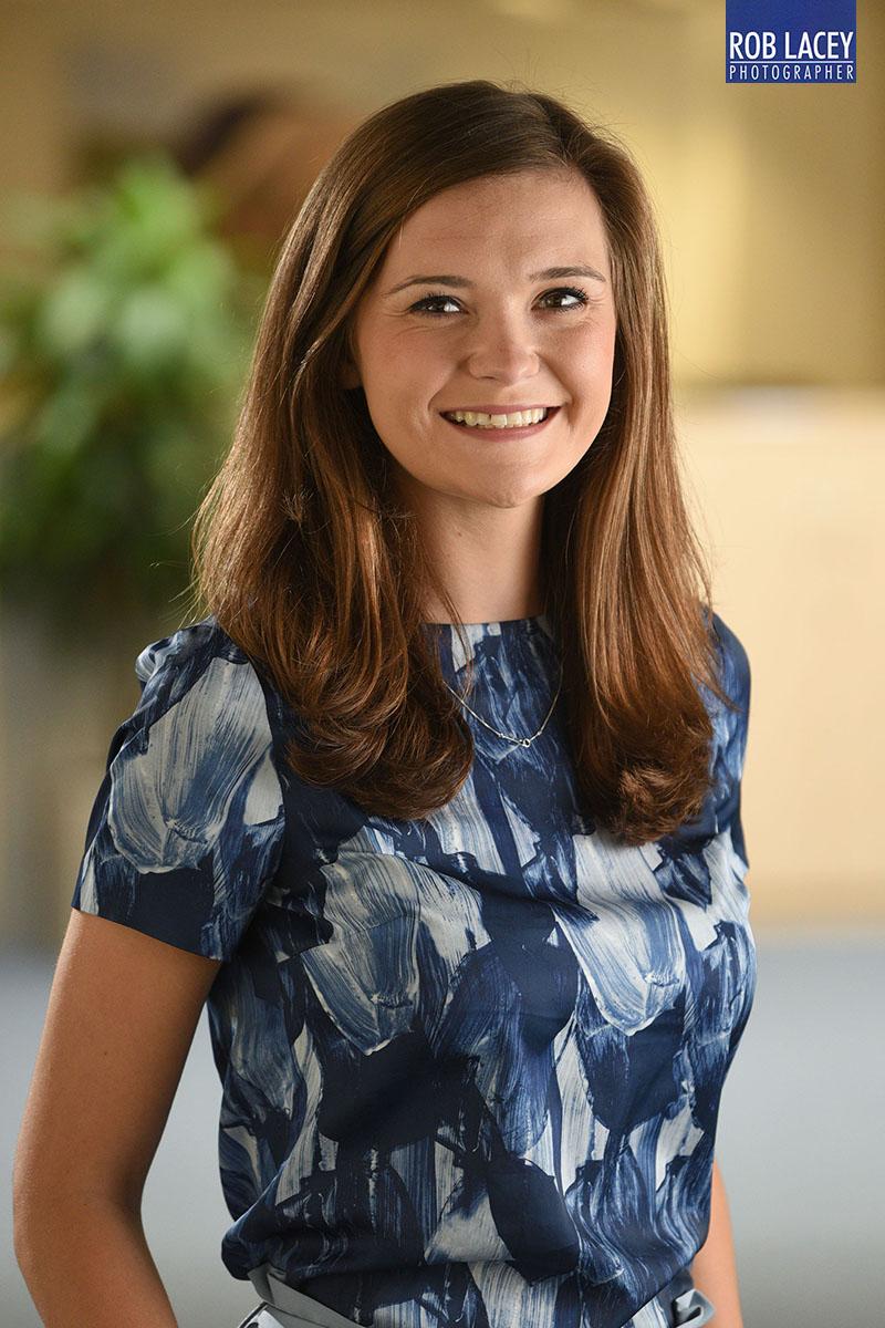 Headshot female office background blue dress 3/4 length