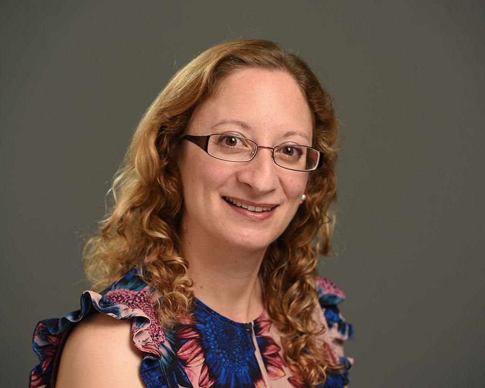female business headshot on grey background
