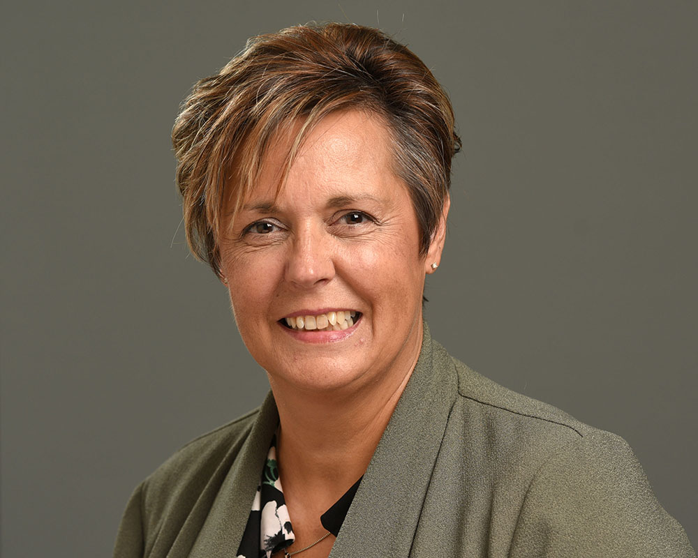Female corporate headshot on grey background