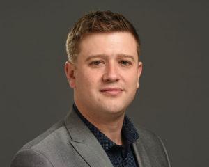 Male business headshot on grey background